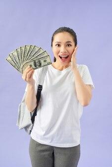 Szczęśliwa dziewczyna student trzyma fan gotówki w banknotach dolarowych robi gest zwycięzcy