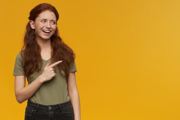 Szczęśliwa dziewczyna szuka, atrakcyjna ruda kobieta z długimi włosami. na sobie zieloną koszulkę. koncepcja emocji. oglądanie i wskazywanie palcem wskazującym w prawo na miejsce na kopię, odizolowane na pomarańczowej ścianie