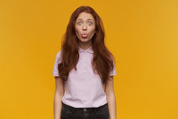 Szczęśliwa dziewczyna szuka, śmieszna ruda kobieta z długimi włosami. ubrana w różową koszulkę. koncepcja ludzi i emocji. pokazuje język. w wesołym nastroju. pojedynczo na pomarańczowej ścianie