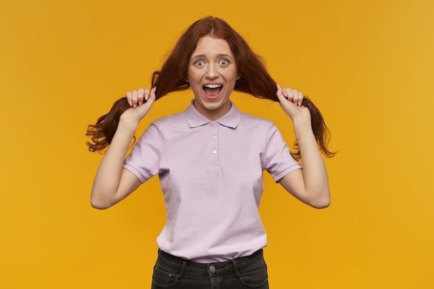 Szczęśliwa dziewczyna szuka, szalona ruda kobieta z długimi włosami. ubrana w różową koszulkę. koncepcja ludzi i emocji. trzyma kosmyki włosów jak warkocze. pojedynczo na pomarańczowej ścianie
