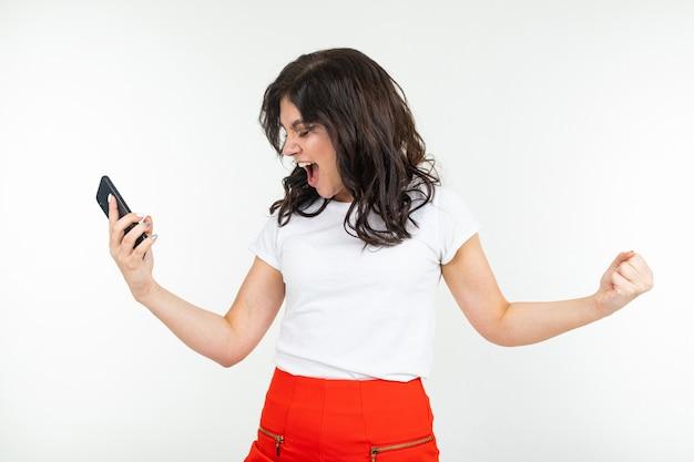 Szczęśliwa dziewczyna tańczy z radością zdając sobie sprawę z wygranej w losowaniu w internecie, trzymając telefon w ręku na białym