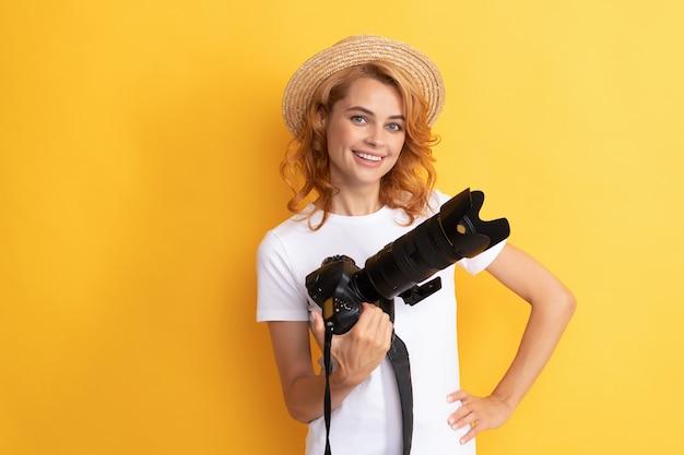 Szczęśliwa dziewczyna trzyma aparat fotograficzny. fotografia amatorska i profesjonalna. letnia sesja zdjęciowa. sesja zdjęciowa. praca fotograficzna. robienie zdjęć. fotografka. ładna kobieta w słomkowym kapeluszu fotografowania.