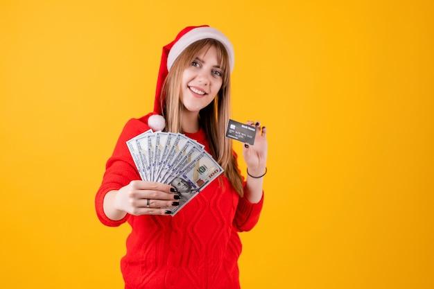 Szczęśliwa dziewczyna trzyma dolarową pieniądze i szablonu kredytową kartę jest ubranym santa kapelusz