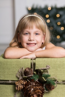 Szczęśliwa dziewczyna trzyma dużego pudełko z prezentem nad jej głową. ferie zimowe, święta bożego narodzenia i ludzi pojęcie