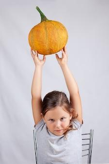 Szczęśliwa dziewczyna trzyma dyni papier-mache nad głową na szarej ścianie