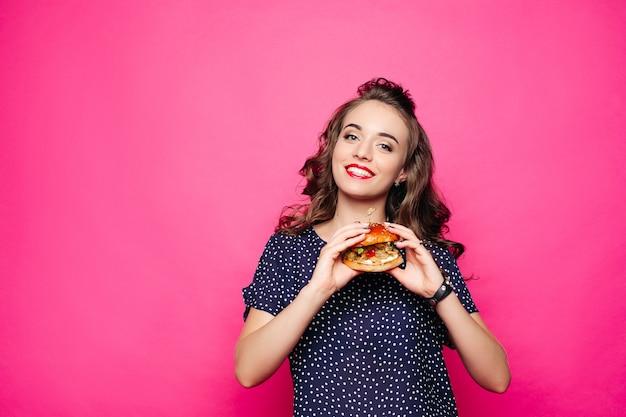 Szczęśliwa dziewczyna trzyma hamburger.