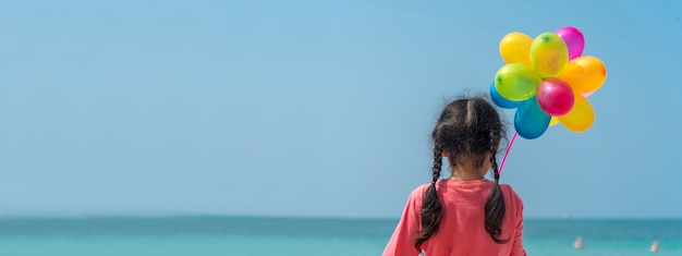 Szczęśliwa dziewczyna trzyma kolorowe balony na plaży. wakacje