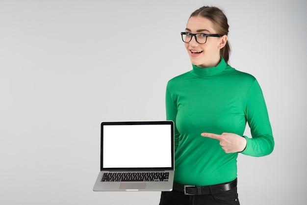Szczęśliwa dziewczyna trzyma laptop i wskazuje ekran. - obraz