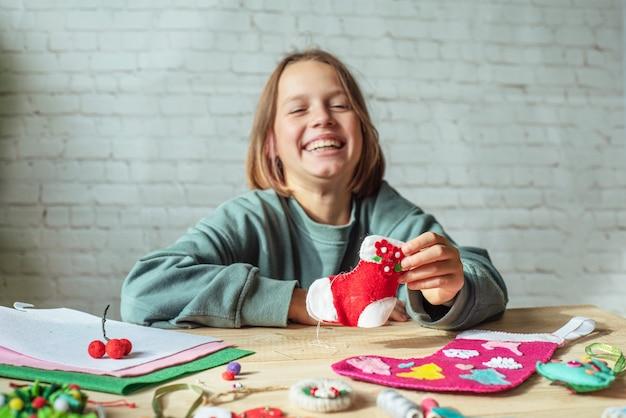 Szczęśliwa dziewczyna trzyma ręcznie robione filcowe skarpety świąteczne, świąteczne rzemiosło