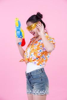 Szczęśliwa dziewczyna trzyma różowego tło wodnego pistolet.