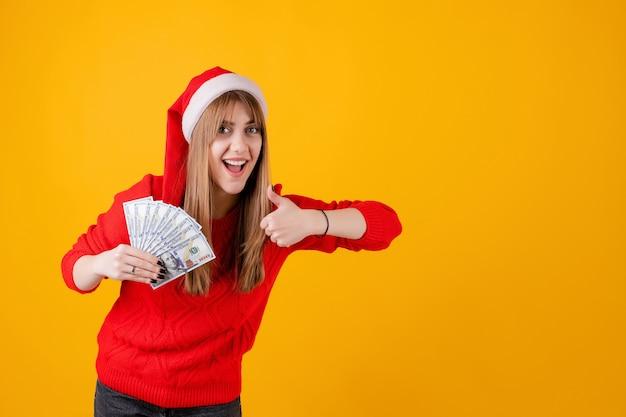 Szczęśliwa dziewczyna trzyma sto dolarowych rachunków w ręce z aprobatami jest ubranym santa kapelusz