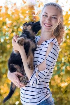 Szczęśliwa dziewczyna trzyma szczeniaka owczarka niemieckiego i uśmiecha się. kupowanie i nabywanie psa. pocałunek psa miłość do zwierząt.