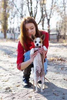 Szczęśliwa dziewczyna trzyma szczeniaka zabawki terier psa ze smyczą na zewnątrz