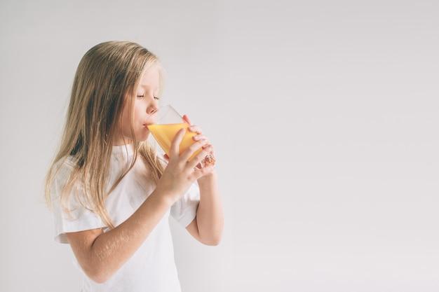 Szczęśliwa dziewczyna trzyma szkło sok pomarańczowy