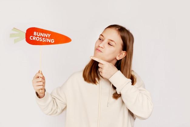 """Szczęśliwa dziewczyna trzyma w rękach marchewkę z napisem """"króliczek"""""""