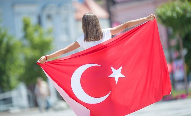 Szczęśliwa dziewczyna turysta spaceru na ulicy z flagą turcji.