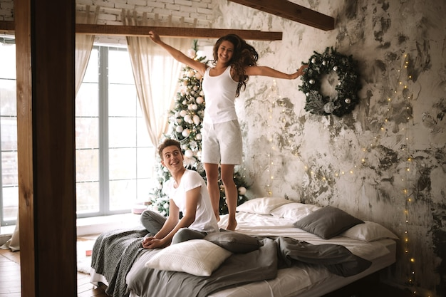 Szczęśliwa dziewczyna ubrana w białe t-shirty i szorty skacze na łóżku obok faceta siedzącego tam w przytulnie urządzonym pokoju z choinką, prezentami i świecami.