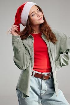 Szczęśliwa dziewczyna ubrana w czapkę i kurtkę czerwoną koszulkę na szarym tle przycięty widok. wysokiej jakości zdjęcie