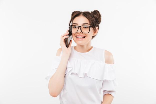 Szczęśliwa dziewczyna ubrana w dwie bułeczki fryzurę i okulary rozmawiająca przez telefon komórkowy i uśmiechająca się z aparatami ortodontycznymi na zębach, odizolowana na białej ścianie