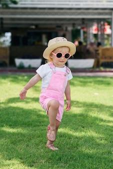 Szczęśliwa dziewczyna ubrana w stylowe jasne ubrania i różowe okulary zabawy na zielonym trawniku. koncepcja letnich wakacji.