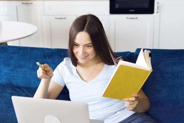 Szczęśliwa dziewczyna uczy się zdalnie online za pomocą laptopa z domu
