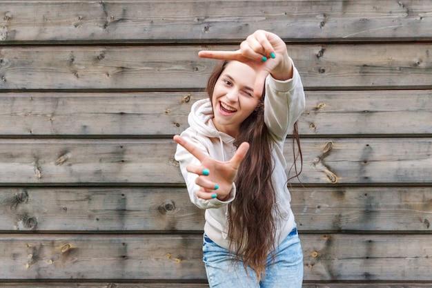 Szczęśliwa dziewczyna uśmiechając się. piękno portret młodej kobiety brunetka roześmiany wyświetlono ramkę palcami na tle ściany drewniane. europejka. pozytywna ludzka emocja wyraz twarzy, język ciała