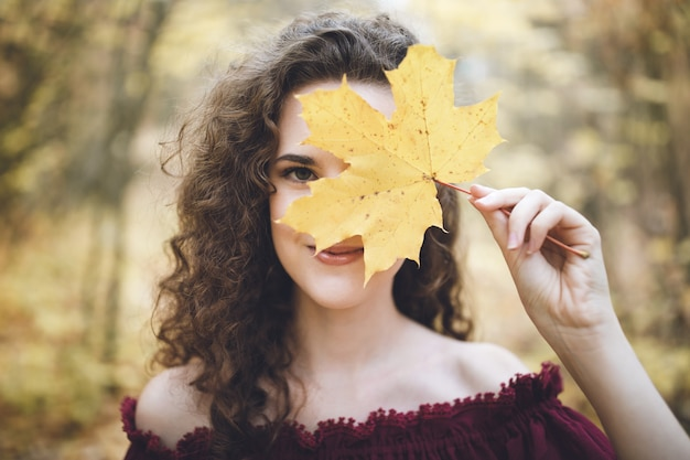 Szczęśliwa dziewczyna w atumn parku trzyma liść klonowy przed jej twarzą
