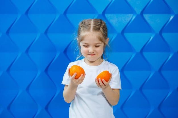 Szczęśliwa dziewczyna w białej koszulce z rozpuszczonymi włosami trzymająca połówki pomarańczy