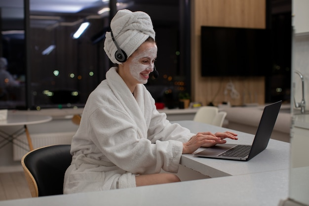 Szczęśliwa dziewczyna w białej szacie i słuchawkach wesoło rozmawiająca przez kamerę internetową na laptopie siedząc w domu wysokiej jakości zdjęcie