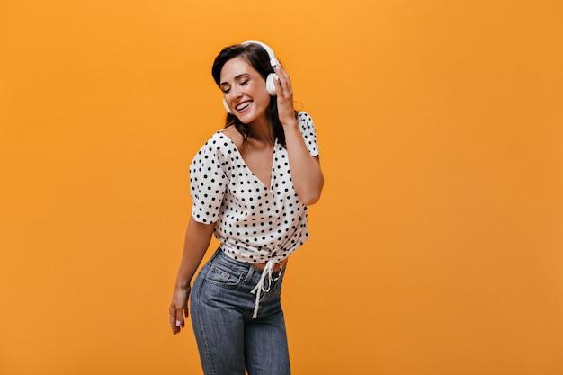 Szczęśliwa dziewczyna w bluzce w kropki słucha muzyki w słuchawkach na pomarańczowym tle. cieszy się uśmiechnięta dorosła dziewczyna w lekkiej koszuli i dżinsach.
