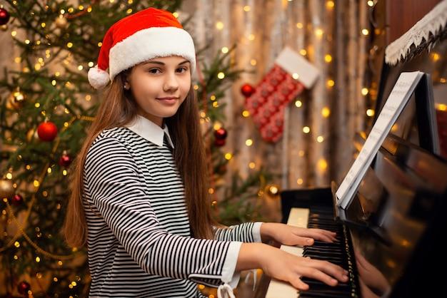 Szczęśliwa dziewczyna w boże narodzenie kapelusz siedzi w pobliżu zdobione jodły i gra na pianinie. nowy rok, święta, czas w domu z koncepcją rodziny.