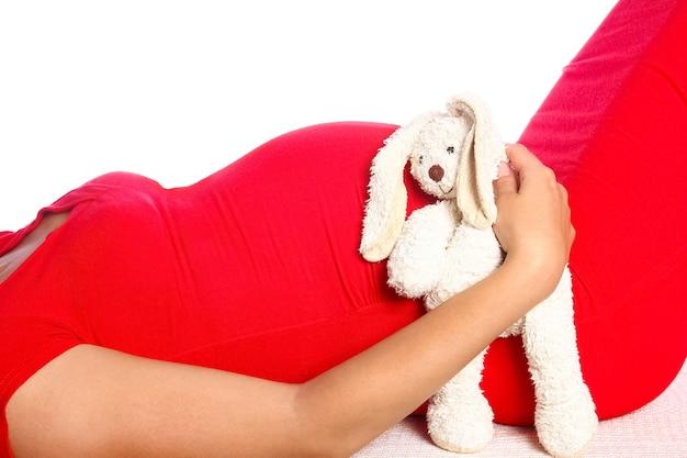 Szczęśliwa dziewczyna w ciąży leży na białej ścianie