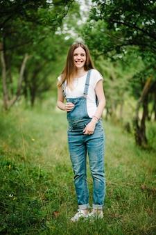 Szczęśliwa dziewczyna w ciąży stać i trzymać ręce na brzuchu, stań na trawie na świeżym powietrzu w ogrodzie