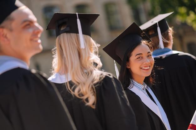 Szczęśliwa dziewczyna w czapce mistrzów, uśmiechając się do swojego przyjaciela w tłumie podczas ceremonii ukończenia szkoły