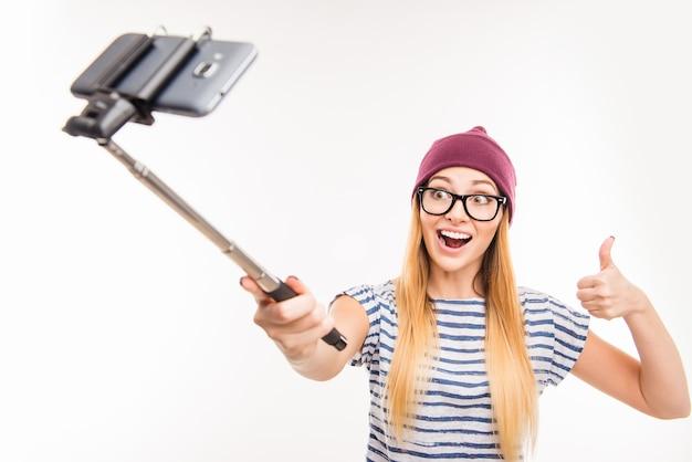 Szczęśliwa dziewczyna w czapkę i okulary biorąc zdjęcie przez kij selfie i kciuki do góry