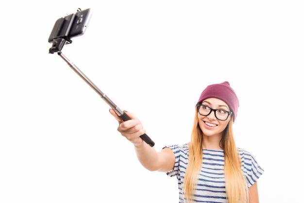 Szczęśliwa dziewczyna w czapkę i okulary biorąc zdjęcie selfie kijem
