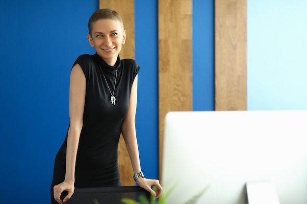 Szczęśliwa dziewczyna w czarnej sukni stoi w biurze