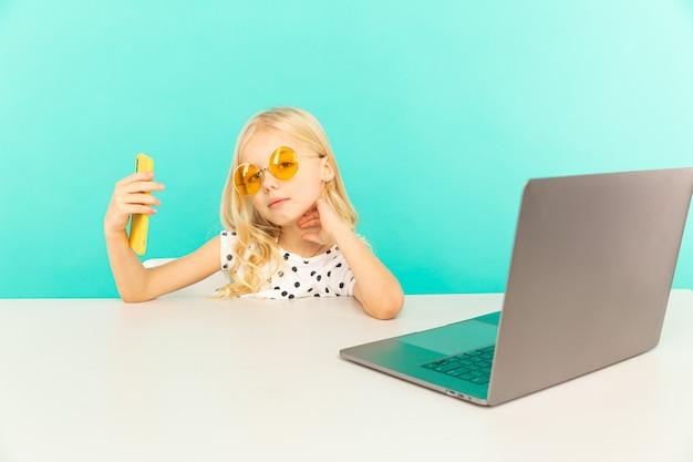 Szczęśliwa dziewczyna w domu, mówiąc przed kamerą na vlog. dziecko robi własne zdjęcia i wideo pracuje jako bloger, nagrywając samouczek wideo do internetu.