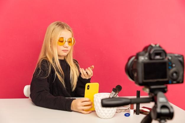 Szczęśliwa dziewczyna w domu, mówiąc przed kamerą na vlog. nastolatka pracująca jako blogerka, nagrywająca samouczek wideo do internetu.