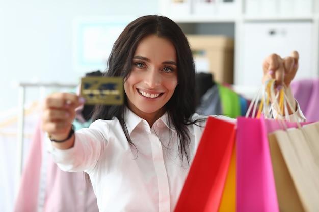Szczęśliwa dziewczyna w domu pokazuje kartę kredytową i pakiety
