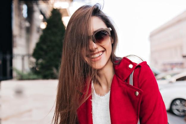 Szczęśliwa dziewczyna w duże okulary przeciwsłoneczne wyrażające enegry podczas ulicznej sesji zdjęciowej