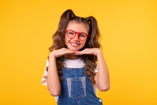 Szczęśliwa dziewczyna w dżinsowym kombinezonie i okularach