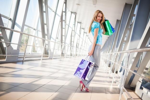 Szczęśliwa dziewczyna w jasnoniebieskiej bluzce i szarych spodniach, stojąc na jednej nodze. futurystyczne wnętrze budynku