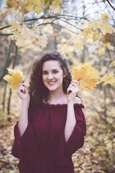 Szczęśliwa dziewczyna w jesień parku trzyma liście klonowych