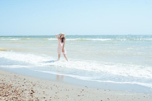 Szczęśliwa dziewczyna w kapeluszu i różowej sukience stoi na falach morza w południe. relaksujące, niezapomniane wakacje na morzu latem