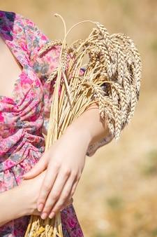 Szczęśliwa dziewczyna w kapeluszu na polu pszenicy. duży kapelusz i długie włosy
