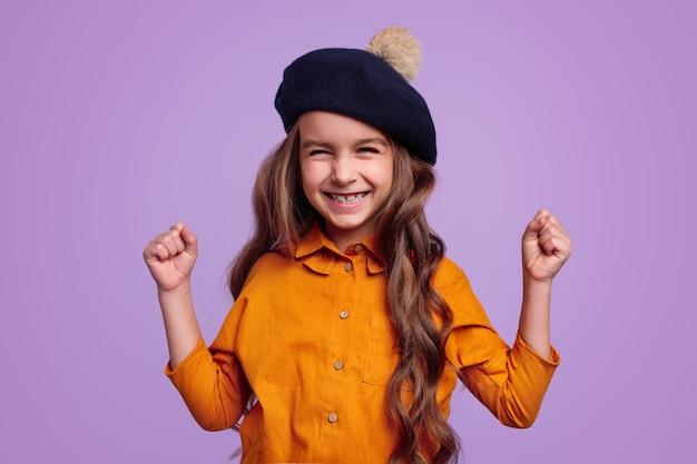 Szczęśliwa dziewczyna w kapeluszu raduje się ze zwycięstwa