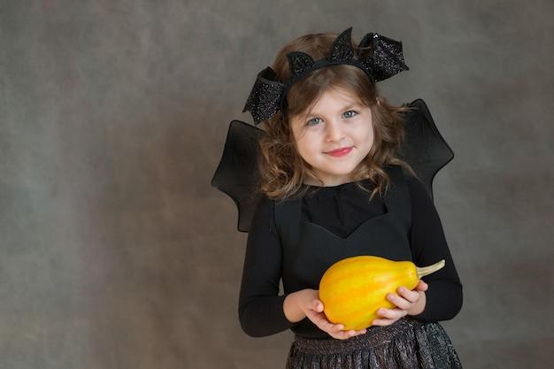 Szczęśliwa dziewczyna w kostium na halloween z żółtą małą dynią na szarej przestrzeni