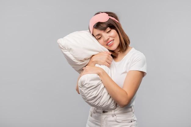 Szczęśliwa dziewczyna w masce do spania, trzymając głowę na poduszce podczas drzemki w izolacji