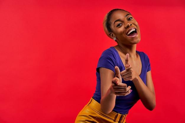 Szczęśliwa dziewczyna w niebieskiej koszulce w kolczykach pozowanie na kamery z wskazującymi palcami wskazującymi